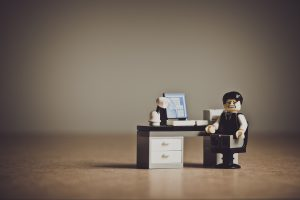 Lego man sitting at desk with pained look on his face