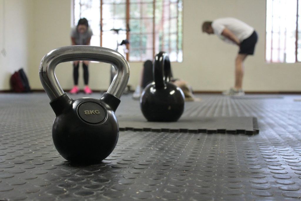 People in rehab session with kettlebells