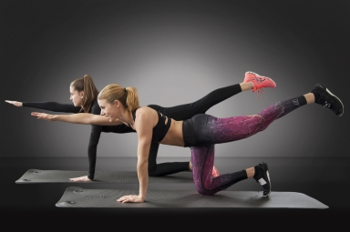 Two women performing the bird-dog exercise for glute strengthening