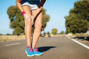 Female runner clutching knee with pain after running